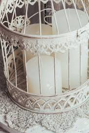 three white christmas candles inside bird cage shabby chic home