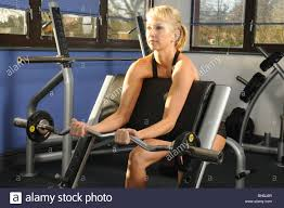in gym doing a preacher curl with ez bar start position