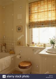 toilet with wooden seat below window with osborne little neutral