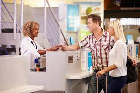 couple at airport check in desk leaving on vacation stock image