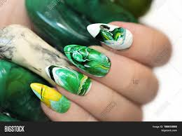 stone nail design in white and green colors with veins of dark and