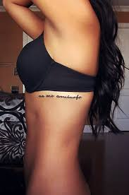 quote tattoo on side lettering and feather tattoo on side