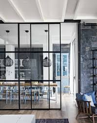 gorgeous floor to ceiling glass divider between kitchen dining szklana scianka ddzielajaca kuchnie od salonu modern monochrome kitchen diner with blue chairs and pendant lights