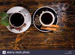 top down view of black tea and coffee garnished with leaves beans