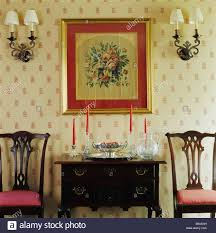 Wallpaper In Dining Room by Wall Lights On Either Side Of Framed Floral Tapestry Above Antique