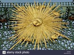 gilded ornament in the shape of the sun with a face on a trellis