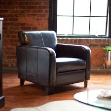 small dark brown leather club chair on wooden floor in exposed
