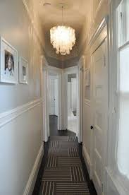 small hallway design with capiz shell chandelier and framed photos