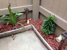 solar lights landscaping small fenced in condo patio border with red lava rock and solar