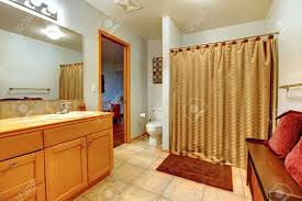 large bathroom interior with bench with red pillows and shower