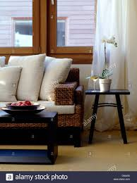 dark wood coffee table in front of rattan sofa with white cushions