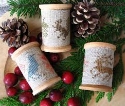 these counted cross stitch wooden spool ornaments would be