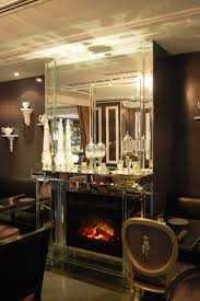 the mantle of the mirrored fireplace is topped with an assortment
