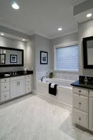 The Master Bathroom Has Black Granite Countertops With Double - Black granite with white cabinets in bathroom