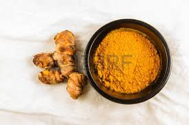 cuisine curcuma of turmeric root or curcuma longa by bowl of turmeric powder