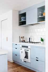 a blue and white galley kitchen creates a functional space that is