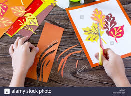 autumn leaves of colored paper on a wooden background the child