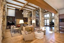 great room with stone columns and light wood flooring great room