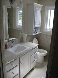 bathroom bathroom with white wooden flatong cabinet over toilet