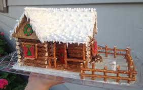 log cabin gingerbread house complete with rustic fence and wood