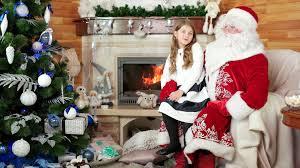 sitting at santa happy kid telling papa noel his