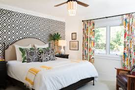 accent wall with geometric wallpaper and colorful drapery in