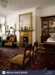 gilt framed mirror above fireplace in edwardian livingroom with