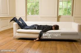 man lying face down on sofa in living room stock photo getty images