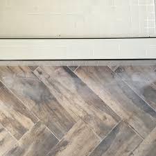 subway tile shower with herringbone wood look tile bathroom floor