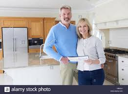 mature couple looking around kitchen of house for sale stock photo