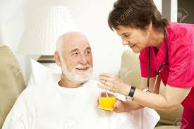 Home Nurse by Home Nurse Giving Her Elderly Patient A Glass Of Orange Juice