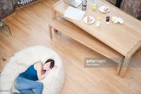 woman on furry bean bag chair in living room stock photo getty