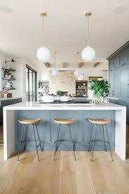 best images about kitchen trends design pinterest modern kitchen with open shelves natural wood barstools blue cabinets white waterfall edged