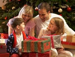 family opening present in front of tree stock photo