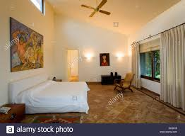large painting above bed with crisp white linen cover in spanish