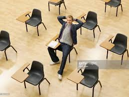 Picture Of Student Sitting At Desk by Confident College Student Sitting At Desk In Classroom Stock Photo