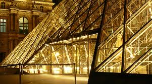 metal frame glass pyramid outside a museum with yellow lights