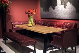wooden dining table big flower vase comfy maroon banquette seating