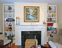 double white wooden bookshelves connected by white fireplace and