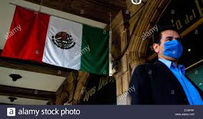 a man wearing a mask walks past a mexican flag in mexico city
