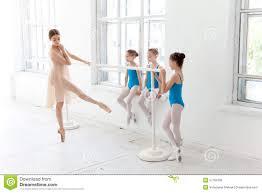 three little ballerinas dancing with personal ballet teacher in