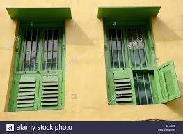 green painted wooden windows yellow painted wall of house kolkata