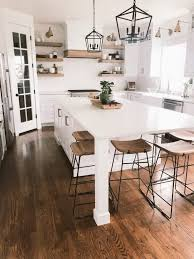 kitchen cabinets on top of floating floor an all white kitchen with island white count black