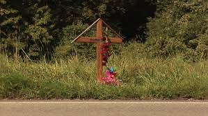 a cross at the side of the road for a person who died in a car