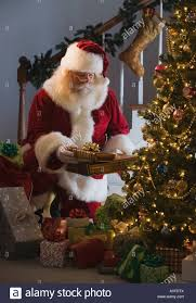 santa claus leaving gifts under christmas tree stock photo