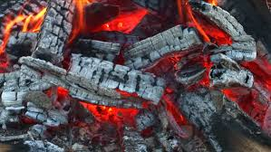 Burning Pit Of Fire - extreme close up of embers and burning wood block in fire pit