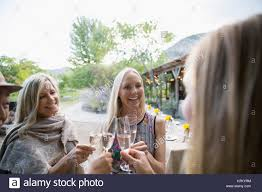 women friends toasting champagne at outdoor dinner party stock