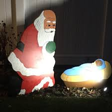 santa praising kneeling praying before manger crib with baby