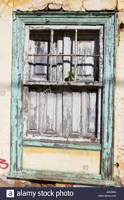 old weathered green painted wooden window frame of abandoned house