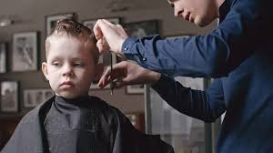 cutting boy hair with scissors professional barber combing and cutting hair of little boy with